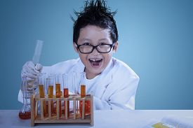 picture of mad scientist  - Cute asian boy wearing lab coat doing experiment like a mad scientist - JPG