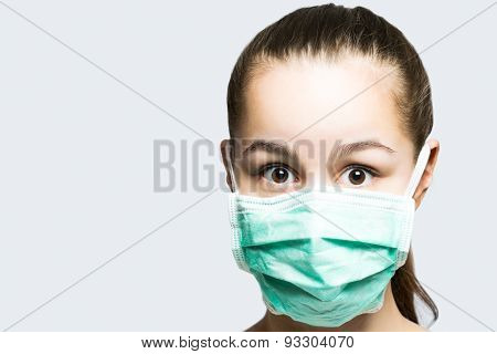 Young girl in doctors mask looking surprised and shocked