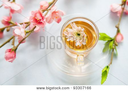 Tea with flowering branches on white table.
