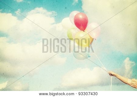and holding multicolored balloons