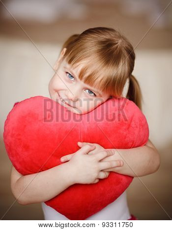 Little Girl Holding Heart-shaped Pillow. Valentines Day. Mothers Day
