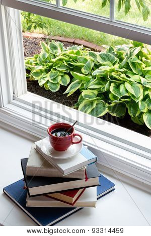 Coffee On Piled Books Next To Glass Window
