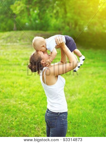 Happy Mother Playing And Having Fun With Baby Outdoors In Sunny Summer Day