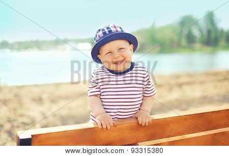 Positive Child Wearing A Hat Having Fun Outdoors On The Beach Near Sea In Sunny Summer Day