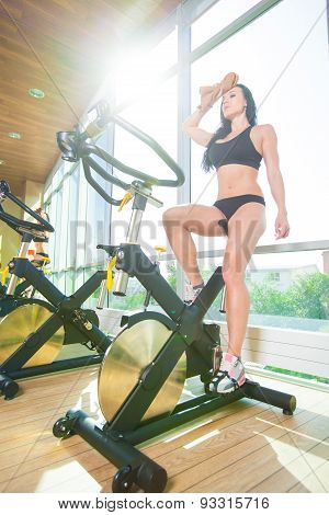 Beautiful woman at the gym on bike, cycle, sunny gym, general plan, weary