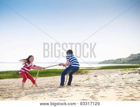 Tug Of War - Boy And Girl Playing On The Beach