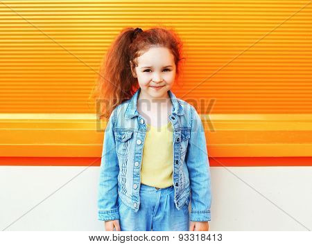 Fashion Kid Concept - Portrait Of Stylish Little Girl Child Wearing A Jeans Clothes In City Against