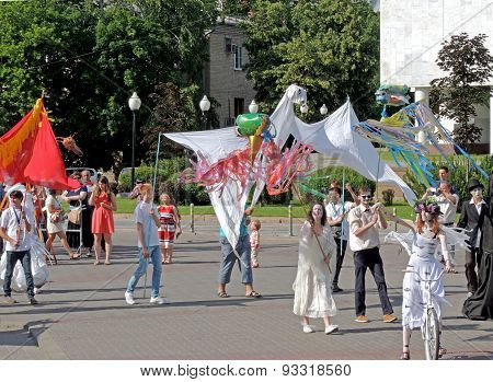 Procession Of Actors In Costumes With Properties On The Square