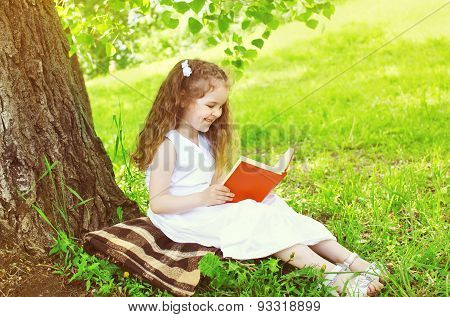 Smiling Little Girl Child Reading A Book On The Grass Near Tree In Sunny Summer Day
