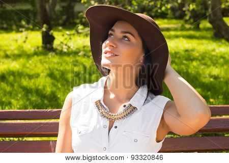 Portrait of an attractive smilling woman with Hat in the Park on a sunny day