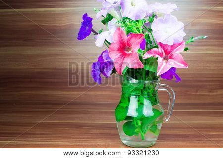 Colorful petunia blooms in a glass pitcher