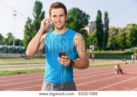 Sportsman standing with mobile phone on stadium