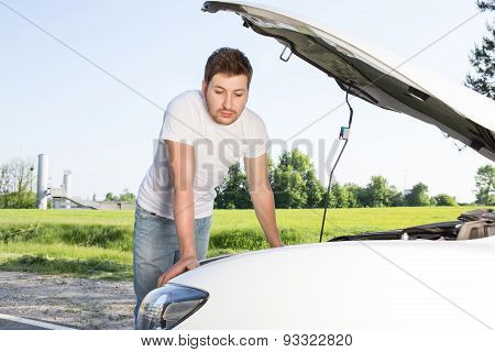 Man leaning on car with opened bonnet