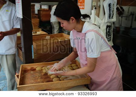 Japanese woman selling traditional japanese pastry at market