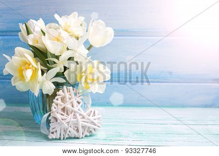 Background With Fresh Narcissus And Tulips In Blue Vase And Heart