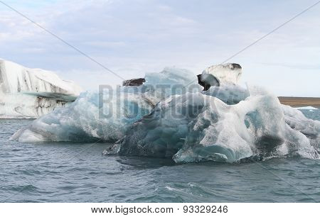 Small Iceberg In Jokulsarlon Under Overcast Sky
