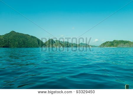 Scenic View Of Rocky Coastline And Lush Mountains