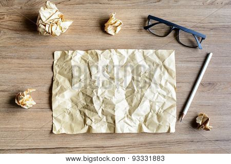 Crumpled Paper Balls With Eye Glasses On Wood Desk
