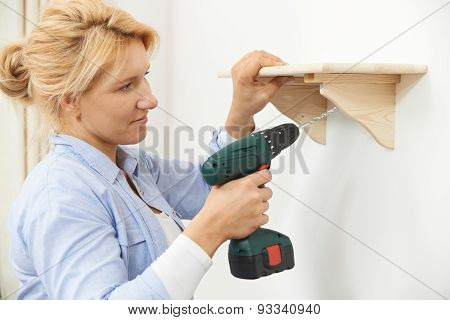 Woman Putting Up Wooden Shelf At Home Using Cordless Drill