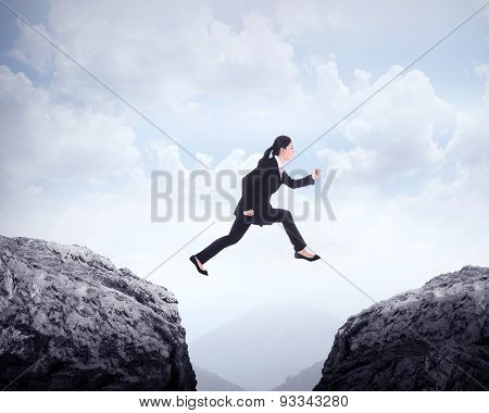 Business Woman Jumping Across Hill
