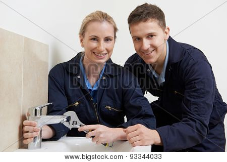 Female Trainee Plumber Working On Tap In Bathroom