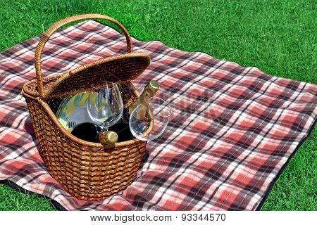 Picnic Basket With Two Wine Bottles On The Red Blanket