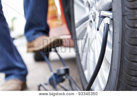 Close Up Of Man Inflating Car Tyre With Foot Pump