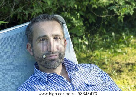 Man Sitting In A Garden With Flower In His Mouth