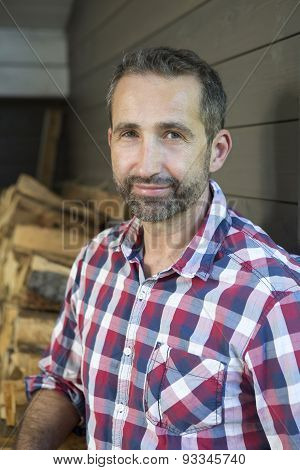 Portrait Of Man In Front Of Firewood