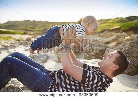 Young Father Playing With Baby Son As Lying At The Beach