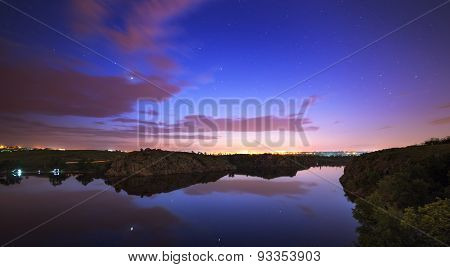Beautiful night sky at the river with stars and clouds