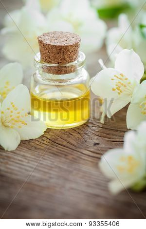 Bottle Of Essential Jasmine Oil And White Jasmin Flowers.