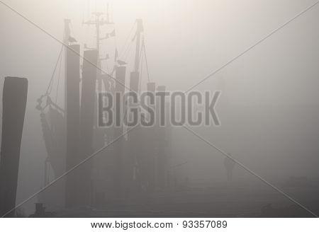 Man Walking On Dock Past Masted Ship In Fog