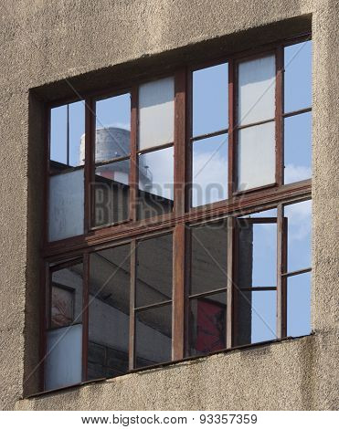 Reflection Of Sky And Industrial Tower In Window