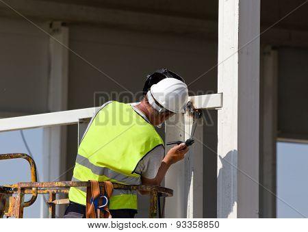 Worker Welding Metal Beams