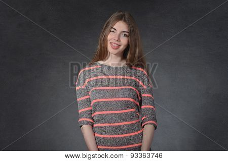 Woman Winking Against A Dark Background