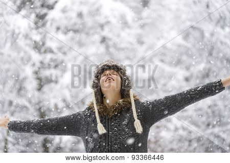 Woman Standing Outdoors In Falling Snow With Her Arms Outspread