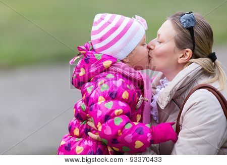 Mother and daughter are kissing each other in the park. (Late fall)