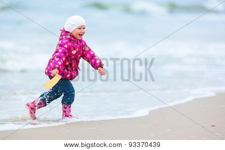 Cute girl is running on the beach