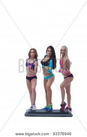 Girls posing with dumbbells standing on stepper
