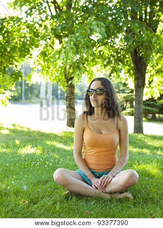 A Young And Quiet Girl Sitting In The Grass.
