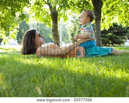 Mother And Son Lying On The Grass.