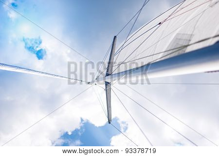 Closeup View Of Mid-size Yacht Mast And Canvas Sail Shot Against Bright Summer Sun.