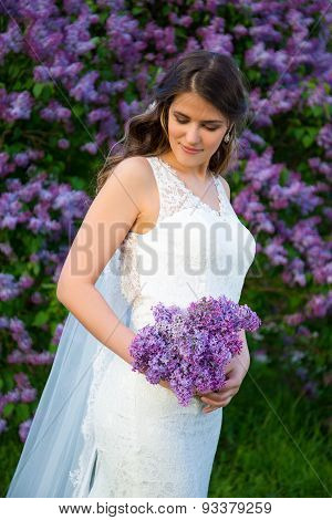 Portrait Of Beautiful Bride With Long Veil Standing Near Lilac Tree