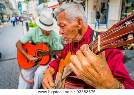 two unidentify indigenous men playing guitar in the commercial street of Armenia, Colombia