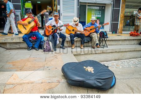 Unidentify indigenous men playing guitar in the commercial street plaza and collectin money of Armen