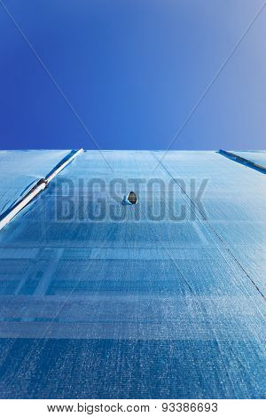 Building With Scaffolding Draped In Blue Debris Netting
