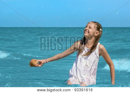 Girl Sitting In Sea Water On The Beach