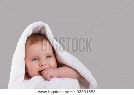 Baby Teething Bites The Hand In A White Towel