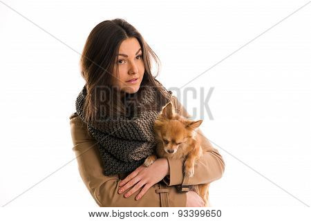 Young Woman With A Gray Scarf And Little Dog Is Looking Straight Ahead